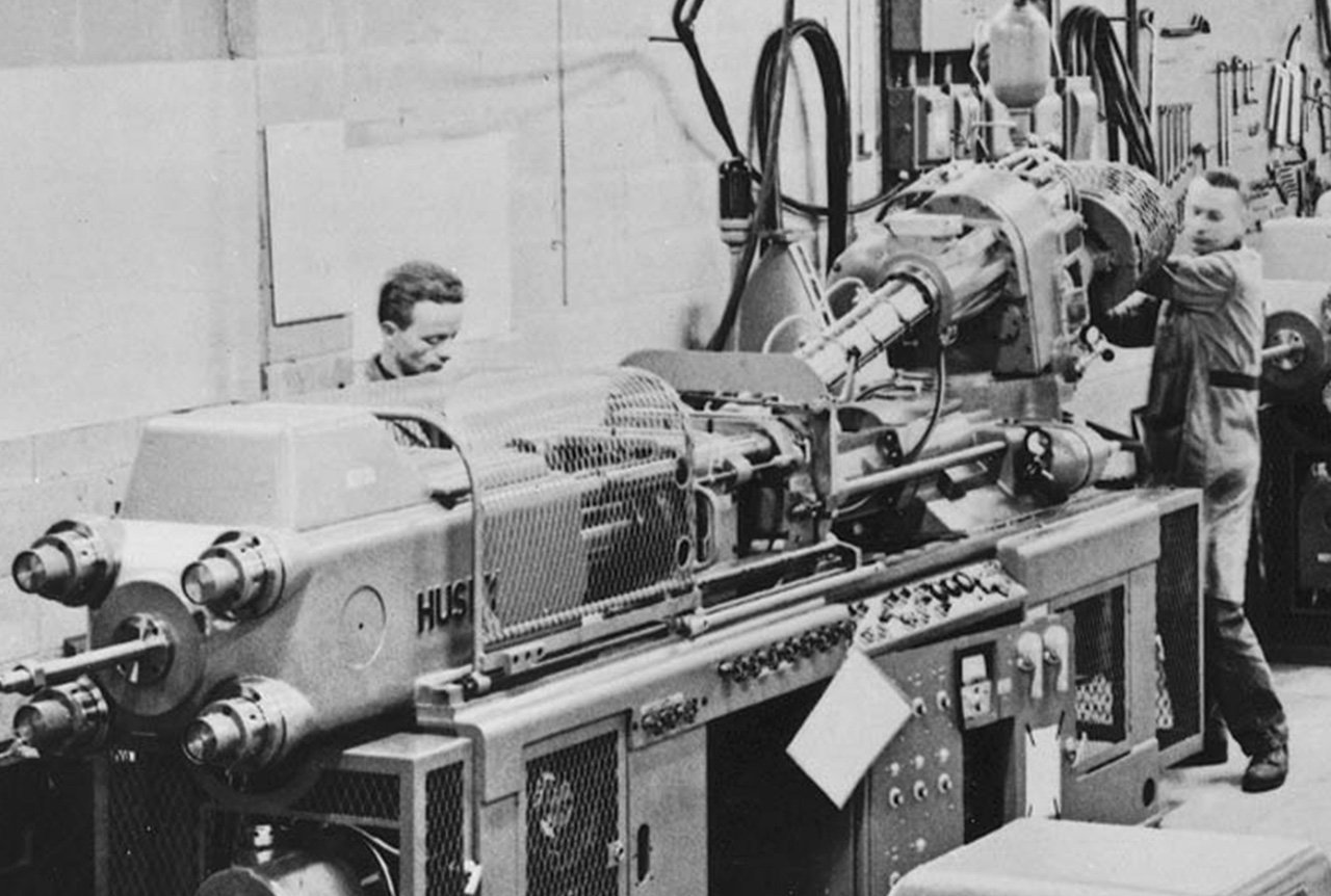 A historical photo of Husky technicians running an injection molding system